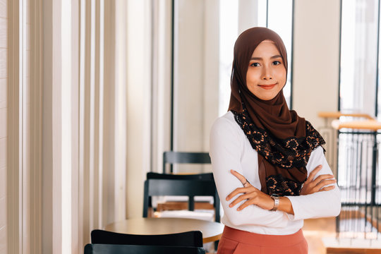 Young happy and successful South East Asian Islamic business woman with arms crossed in business corporate building setting looks at camera. She wears head scarf or hijab and modern elegant clothes