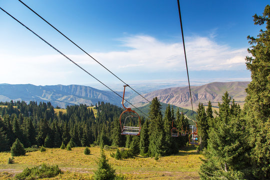 Summer mountain landscape high in the mountains. Tall trees of Christmas trees, ski lift at the ski base.