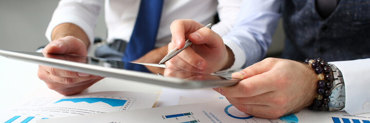 Group of businessmen point finger and silver pen in arms using electronic pad pc closeup. Financial stock market data management job remote bank or e-commerce application modern lifestyle
