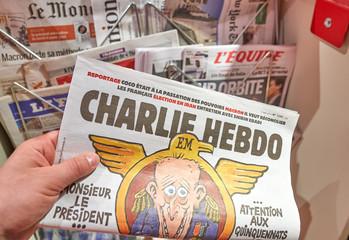 A hand holding Charlie Hebdo