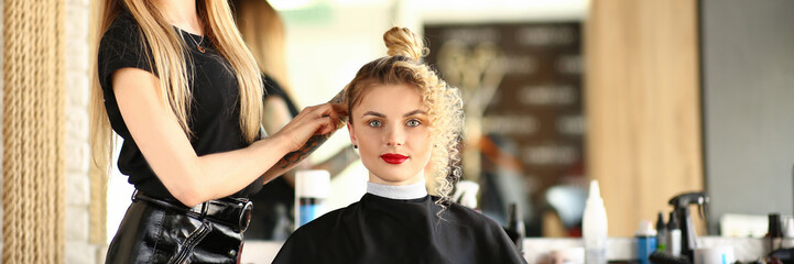Hairdresser hands hold curling iron and make wave to blonde customer portrait