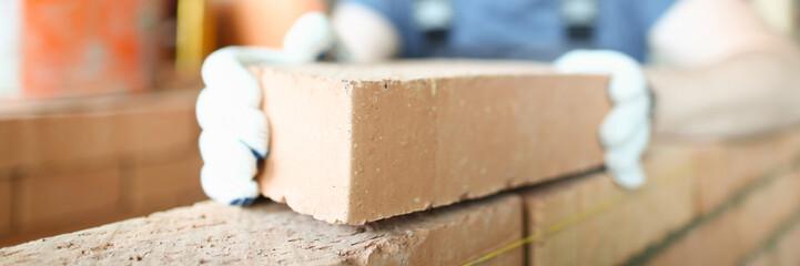 Male smiling builder puts make brickwork repair closeup. Sale of building materials concept.