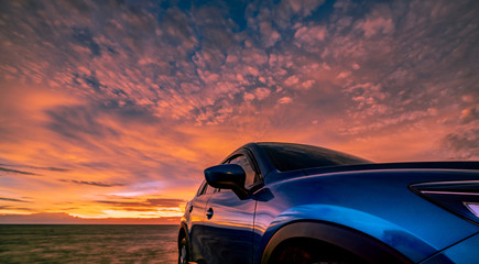 Blue compact SUV car with sport, modern, and luxury design parked on concrete road by the sea at sunset. Front view of beautiful electric car. Driving with confidence. Travel on vacation at the beach.