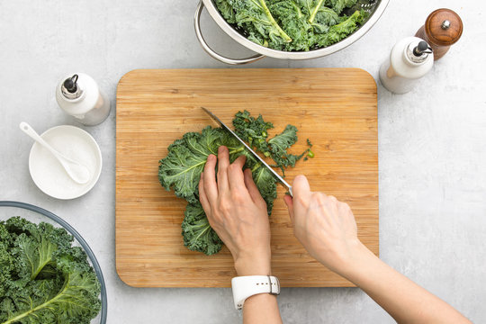 Top down view of fresh kale leaves cut on a cutting board