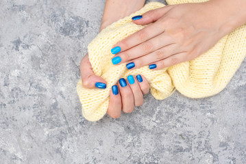Nails of women covered in blue lacquer different shades with rhinestones and with flowers in his hand.
