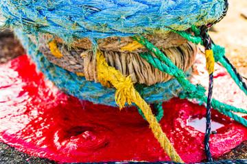 Harbor marina detail. Old rusty mooring bollard with rope. Berth in the passenger port. Mooring points.