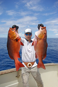 deep sea fishing, man holding two red snapper. Boat fishing, big game
