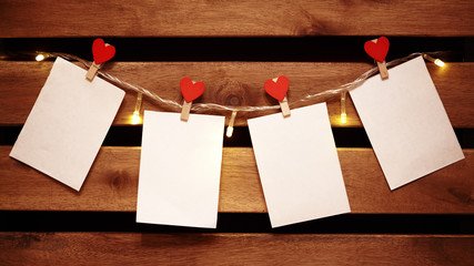 Blank White Stickers hanging on Light Garland with Decorative Love Pins. Cozy Valentines Day Background with Copy Space