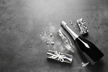 Flat lay composition with bottle of champagne for celebration on grey stone background. Space for text