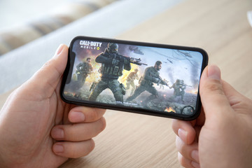 Man hand holding iPhone 11 game Call of Duty Mobile