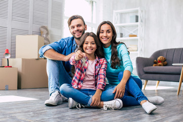 New life starts now. Appealing family are sitting on the floor, holding keys of their new apartment, and enjoying their new life in the new house.