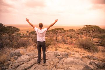 Man at view point looking to the bush savannah of Serengeti at sunset, Tanzania - Safari in Africa