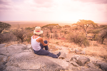 Girl at view point looking to the bush savannah of Serengeti at sunset, Tanzania - Safari in Africa
