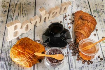 Pain au chocolat et croissant pur beurre, viennoiseries artisanales avec le mot bonheur sculpté dans un morceau de bois sur une table en bois avec du miel de la confiture et un café expresso