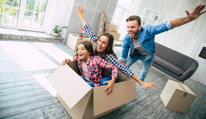 Family of three is playing in their new apartment after the house moving, young bearded father is riding his wife and daughter in a box, which was just emptied from their personal items.