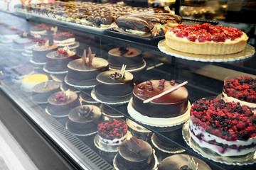 Different delicious cakes on display in cafe, view through window