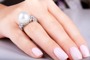 Wall Mural - Gold ring with diamonds and pearl. Beautiful female hands with diamond ring with pearl. Diamond ring with pearl. Woman's nails with manicure. White gold.
