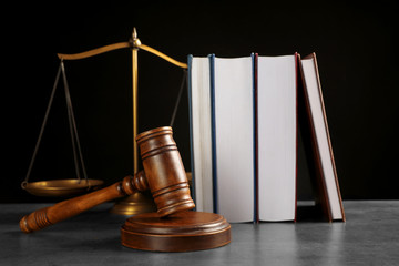 Judge's gavel, books and scales on grey table against black background. Criminal law concept