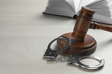 Judge's gavel, handcuffs and book on white wooden background. Criminal law concept