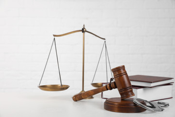 Composition with gavel and handcuffs on table against white background. Criminal law