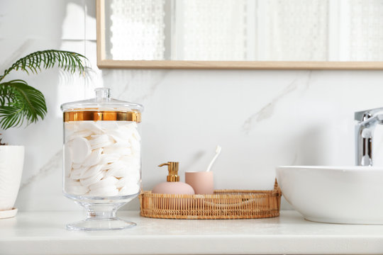 Jar with cotton pads on bathroom countertop