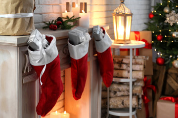 Red Christmas stockings with gifts on decorative fireplace indoors. Festive interior
