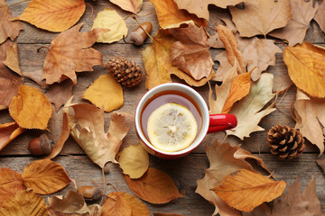Flat lay composition with cup of hot drink on wooden table. Cozy autumn atmosphere