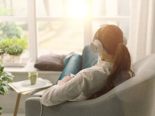 Woman relaxing on the couch and listening to music