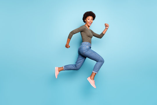 Full length body size photo of cheerful fast quick black woman jumping running towards shopping mall as rapidly as possible wearing jeans denim isolated over vivid blue color background
