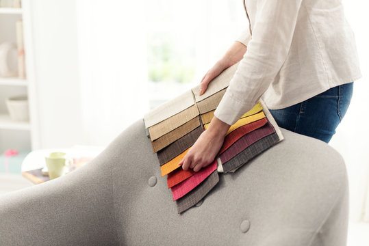 Professional decorator choosing the best upholstery for the armchair