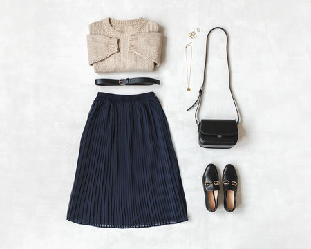Blue midi pleated skirt, beige knitted sweater, small black cross body bag, belt, loafers (flat shoes) on grey background. Overhead view of women's casual day outfit. Flat lay, top view. Women clothes