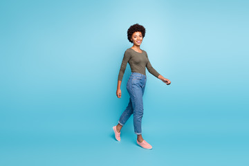 Full length body size photo of cheerful cute charming nice black woman going turned walking smiling friendly toothily isolated over vivid color blue background Wall mural