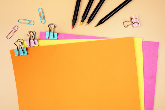 Orange empty sheet of paper mockup. Copy space. Binder clip with colored papers