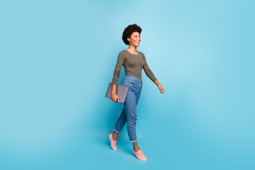 Full length photo of positive cheerful afro american girl hold her netbook go university for education learning wear casual style outfit denim jeans pink sneakers isolated blue color background
