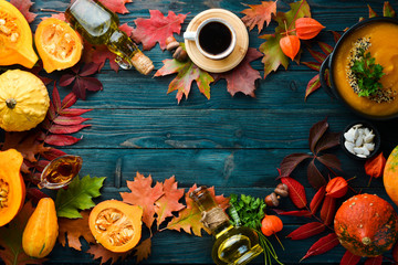 Autumn background with coffee, pumpkin, autumn leaves. flat lay. On a blue wooden background. Top view. Free space for your text.
