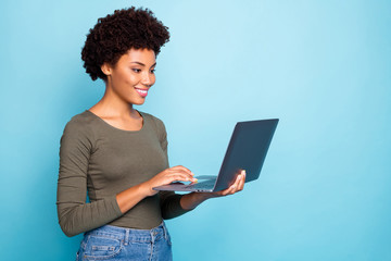Portrait of positive cool confident afro american girl freelancer use laptop type emails chat with her partners business clients wear green style clothes denim jeans isolated blue color background