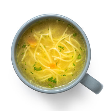 Instant chicken noodle soup in a grey ceramic mug isolated on white. Top view.