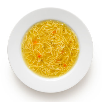 Instant chicken noodle soup in a white ceramic soup plate isolated on white. Top view.