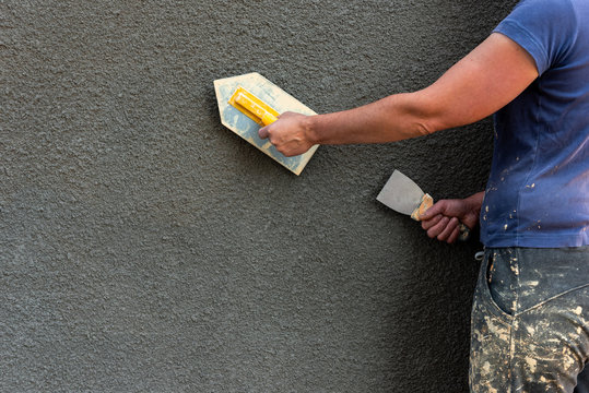 Application of decorative plaster on wall using construction tool.
