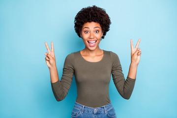 Fototapete - Wow hi friends. Portrait of excited amazed afro american girl meet her fellows enjoy feel candid make v-signs wear youth style sweater denim jeans isolated over blue color background