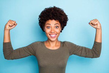 Portrait of amazed crazy mulatto girl show muscles impressed by her power scream wow omg wear casual style clothes isolated over blue color background