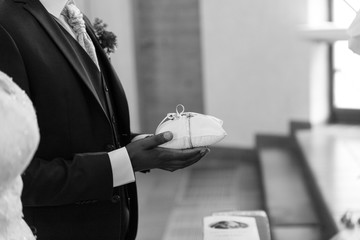 Groom holding a pillow with golden wedding rings in front of the altar