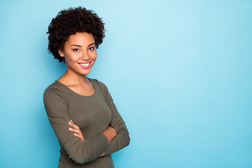 Turned photo of positive cheerful successful mulatto girl true leader on her enterprise cross hands wear green pullover outfit isolated over blue color background