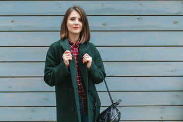 Young stylish brunette woman with short haircut, wearing red plaid shirt, green coat, black backpack standing near blue wooden wall on the city streets. Trendy casual outfit. Street fashion.