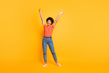 Full length body size photo of charming cute cheerful attractive rejoicing overjoyed girlfriend black skinned wearing jeans denim raising her hands up while isolated yellow vibrant color background