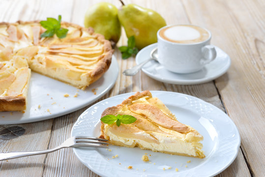 Home baked French style dessert pear tart with curd cheese, served with a cup of cappuccino