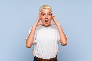 Teenager girl with white short hair over blue wall with surprise expression