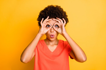 Photo of charming nice cute attractive girlfriend fooling pretending to wear glasses with fingers round her eyes wearing orange t-shirt isolated over yellow vibrant color background