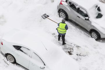 Man shoveling snow after snowfall on parking near car