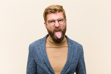 young blonde businessman feeling disgusted and irritated, sticking tongue out, disliking something...
